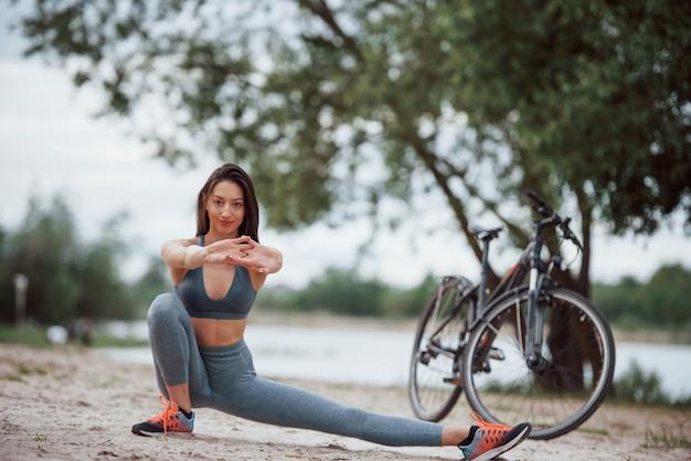 Met de handen naar voren. wielrenster met een goede lichaamsvorm die yoga-oefeningen doet en zich uitstrekt in de buurt van haar fiets op het strand overdag