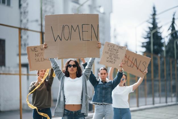 Met de handen omhoog. een groep feministische vrouwen protesteert buitenshuis voor hun rechten