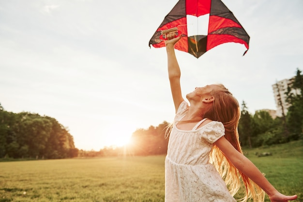 Met de rechterhand vasthouden. gelukkig meisje in witte kleren veel plezier met vlieger in het veld. prachtige natuur.