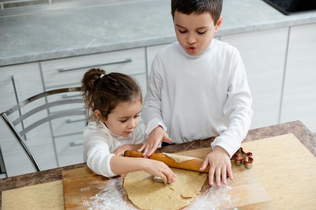 Met de speciale vormen snijden de kinderen uit de kerstkoekjes
