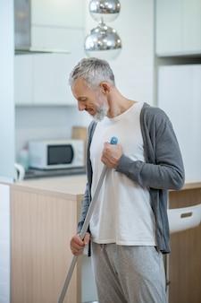 Met een dweil. man in homewear die het huis schoonmaakt en een dweil vasthoudt