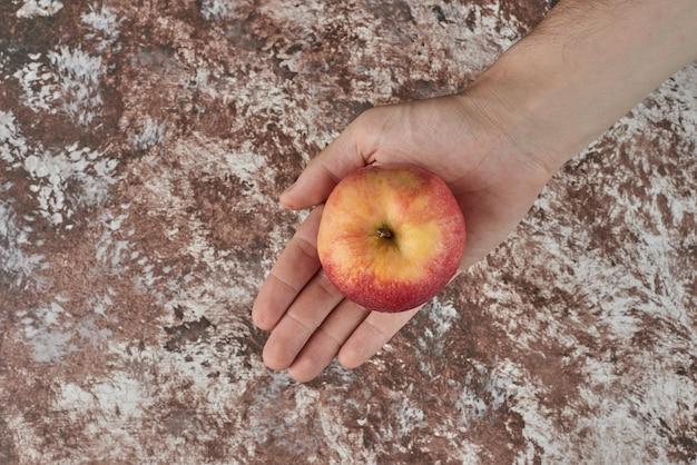 Met een gele appel in de hand.