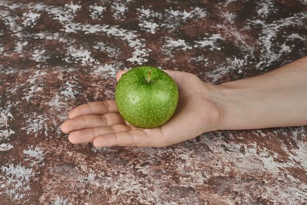 Met een groene appel in de hand.