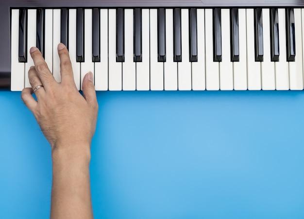 Met één hand toetsen spelen op muziektoetsenbord met blauwe kopie ruimte