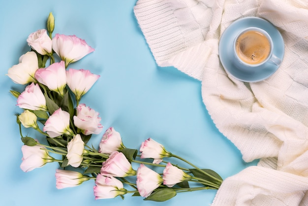 Met een kopje koffie, bloemen eustoma op deken op een blauwe achtergrond, plat leggen kopie ruimte.