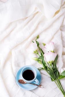 Met een kopje koffie met chocolade, bloemen eustoma op deken in bed.