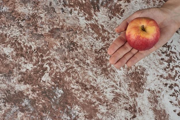 Met een rode appel in de hand.