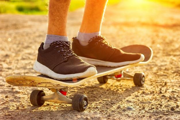 Met een skateboard rijdend op de weg bij zonsondergang, de zomervermaak