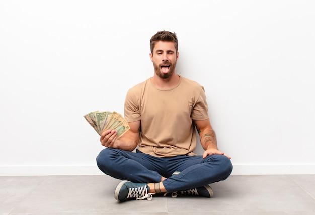 Met een vrolijke, zorgeloze, opstandige houding, een grapje en tong uitsteken, plezier hebben met het vasthouden van dollarbiljetten