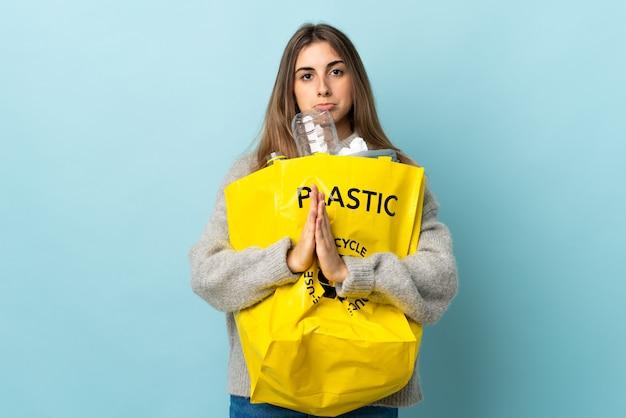 Met een zak vol plastic flessen om te recyclen over geïsoleerde blauwe smeekbeden