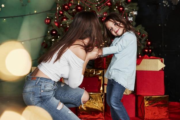 Met elkaar spelen. vrolijke moeder en dochter zitten in de buurt van de kerstboom die erachter.