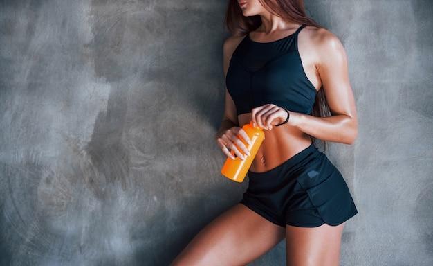 Met flesje water. jonge fitness vrouw met slank type lichaam en in zwarte sportieve kleding is in de sportschool.