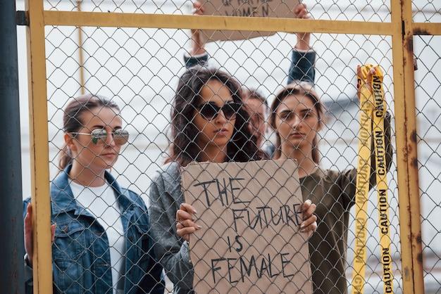 Met geel gekleurd waarschuwingsband. een groep feministische vrouwen protesteert buitenshuis voor hun rechten