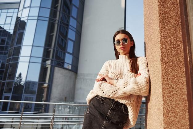 Met gekruiste armen. mooi meisje in warme kleren lopen in het weekend in de stad