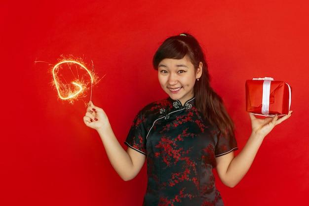 Met geschenkdoos en helder sterretje. gelukkig chinees nieuwjaar. aziatisch jong meisje portret op rode achtergrond. vrouwelijk model in traditionele kleding ziet er gelukkig uit. copyspace.