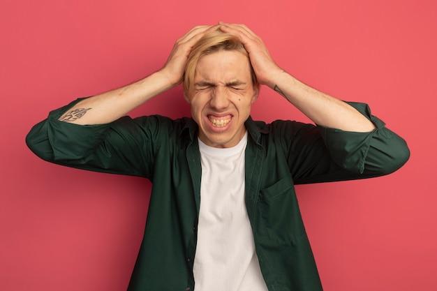 Met gesloten ogen betreurd dat jonge blonde man met een groen t-shirt zijn hoofd vastgreep