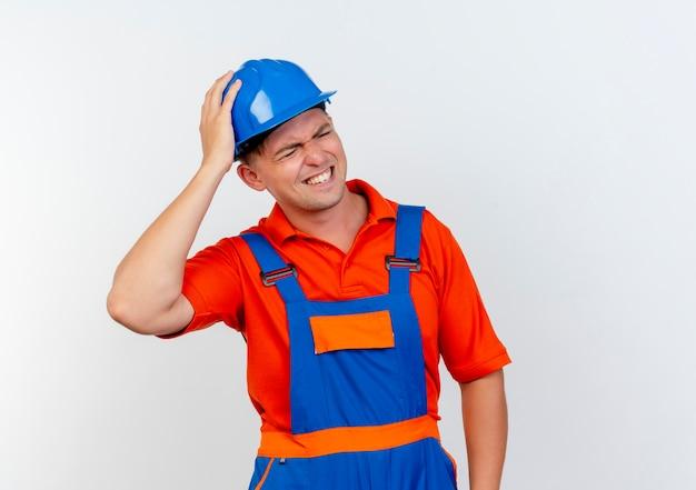 Met gesloten ogen betrokken jonge mannelijke bouwer die uniform en veiligheidshelm draagt die hand op hoofd op wit zetten