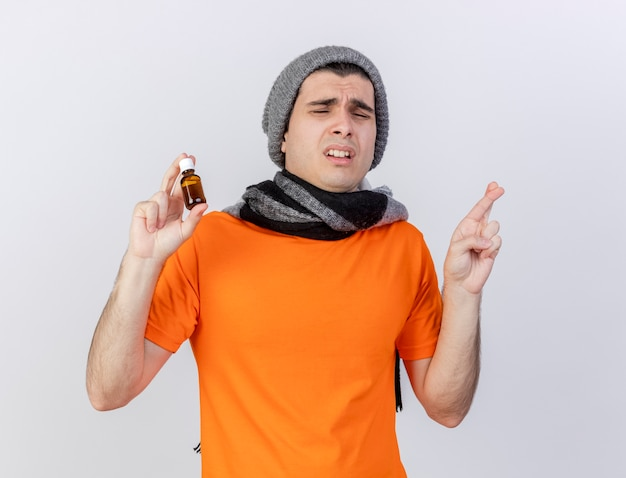 Met gesloten ogen bezorgde jonge zieke man met wintermuts met sjaal medicijn in glas vasthouden