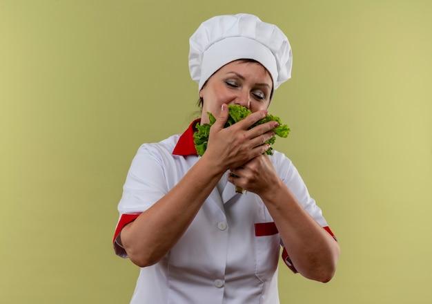 Met gesloten ogen bijt de vrouwelijke kok van middelbare leeftijd in eenvormige chef-kok salade in haar hand