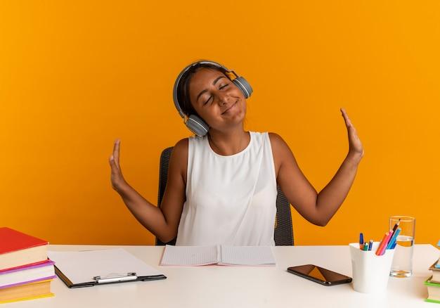 Met gesloten ogen blij jong schoolmeisje zittend aan een bureau met school tools luisteren muziek op koptelefoon en spreid handen geïsoleerd op oranje muur