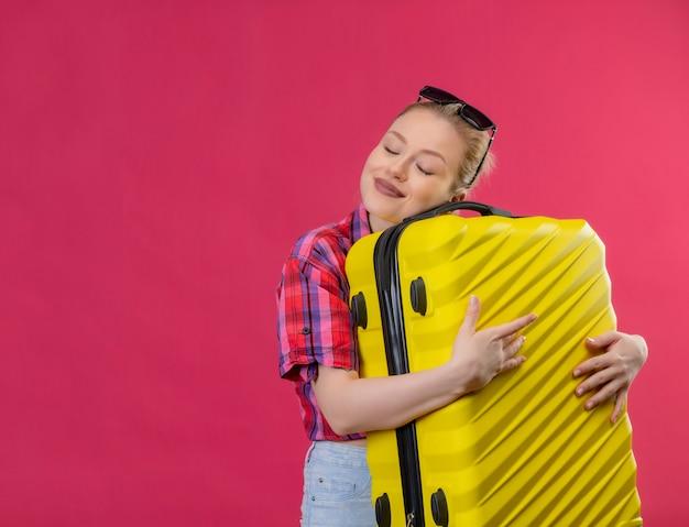 Met gesloten ogen glimlachend reiziger jong meisje die rood overhemd in glazen dragen die koffer op geïsoleerde roze achtergrond houden