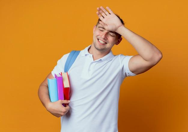 Met gesloten ogen glimlachende jonge knappe mannelijke student die achterzak met boeken draagt