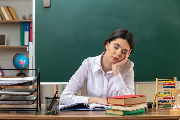 Met gesloten ogen hand op hand jonge vrouwelijke leraar zittend aan tafel met schoolhulpmiddelen in de klas
