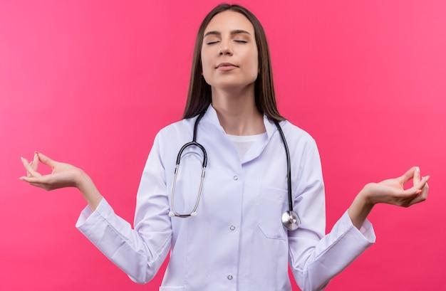 Met gesloten ogen jong artsenmeisje die stethoscoop medische toga dragen die okgebaar op geïsoleerde roze muur tonen