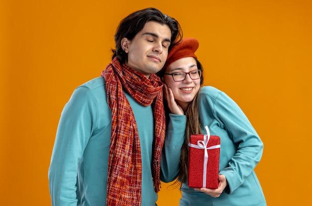 Met gesloten ogen jong koppel op valentijnsdag man met sjaal meisje met geschenkdoos geïsoleerd op oranje achtergrond