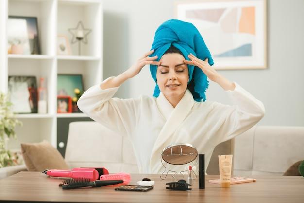 Met gesloten ogen, jong meisje gewikkeld haar in een handdoek en brengt tonercrème aan, zittend aan tafel met make-uptools in de woonkamer