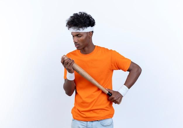Met gesloten ogen jonge afro-amerikaanse sportieve man met hoofdband en polsbandje met vleermuis