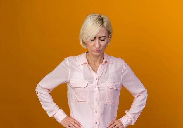 Met gesloten ogen jonge blonde slavische vrouw die hand op heup zet die op oranje muur wordt geïsoleerd