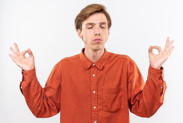 Met gesloten ogen jonge knappe kerel die rood overhemd draagt die meditatie doet