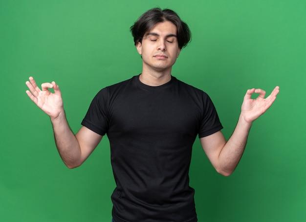 Met gesloten ogen jonge knappe kerel die zwart t-shirt draagt dat meditatiegebaar toont dat op groene muur wordt geïsoleerd