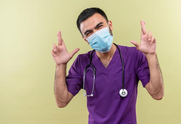 Met gesloten ogen jonge mannelijke arts die paarse chirurgenkleding en een stethoscoop medisch masker draagt dat de vingers kruist op geïsoleerde groene muur