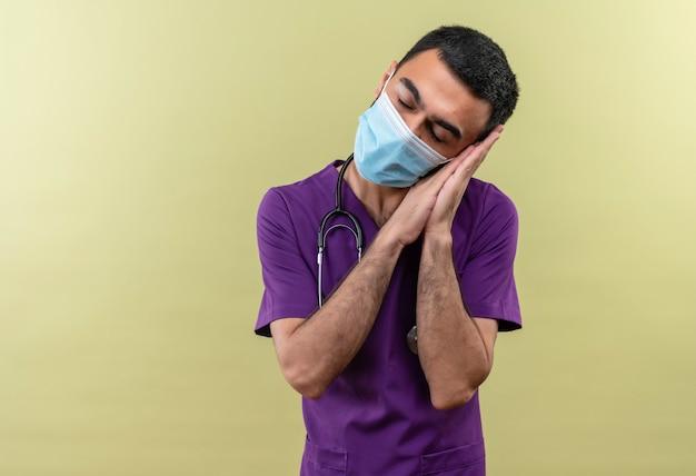 Met gesloten ogen jonge mannelijke arts die paarse chirurgenkleding en een stethoscoop medisch masker draagt dat slaapgebaar op geïsoleerde groene muur toont