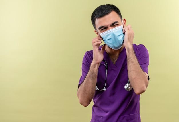 Met gesloten ogen jonge mannelijke arts die paarse chirurgenkleding en een stethoscoop medisch masker draagt met gesloten oren op geïsoleerde groene muur
