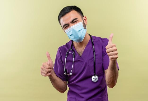Met gesloten ogen jonge mannelijke arts die paarse chirurgenkleding en een stethoscoop medisch masker draagt, zijn duimen omhoog op geïsoleerde groene muur
