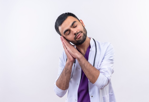 Met gesloten ogen jonge mannelijke arts die stethoscoop medische toga draagt die slaapgebaar op geïsoleerd wit toont