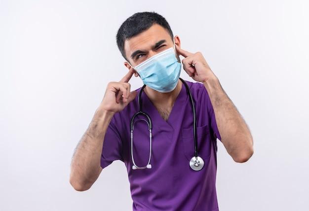 Met gesloten ogen jonge mannelijke arts paarse chirurg kleding en stethoscoop medische masker dragen gesloten oren op geïsoleerde wit