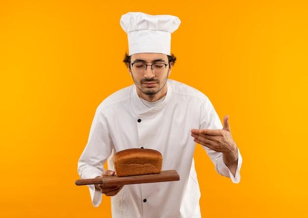 Met gesloten ogen jonge mannelijke kok die eenvormige chef-kok en glazen draagt die en brood op scherpe raad houden die op gele muur wordt geïsoleerd