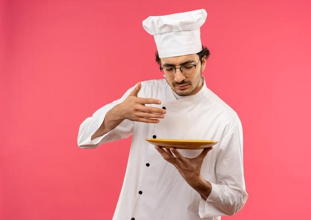 Met gesloten ogen jonge mannelijke kok die eenvormige chef-kok en glazen draagt die het snuiven maaltijd op voedsel beweren dat op roze muur wordt geïsoleerd