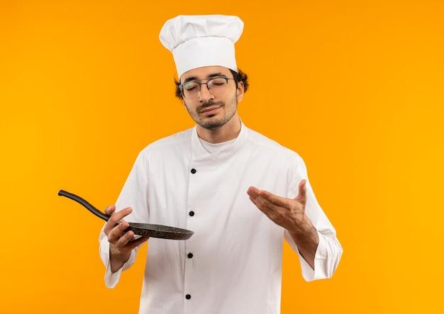 Met gesloten ogen jonge mannelijke kok die eenvormige chef-kok en glazenholding draagt en met hand aan koekenpan wijst die op gele muur wordt geïsoleerd