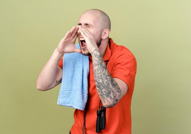 Met gesloten ogen jonge sportieve man met handdoek en springtouw op schouder iemand bellen geïsoleerd op olijfgroene muur