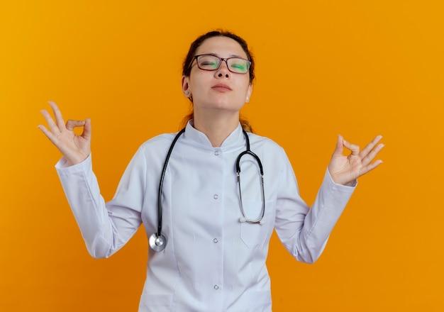 Met gesloten ogen jonge vrouwelijke arts die medische mantel en stethoscoop met bril draagt die meditatie toont die op oranje muur wordt geïsoleerd
