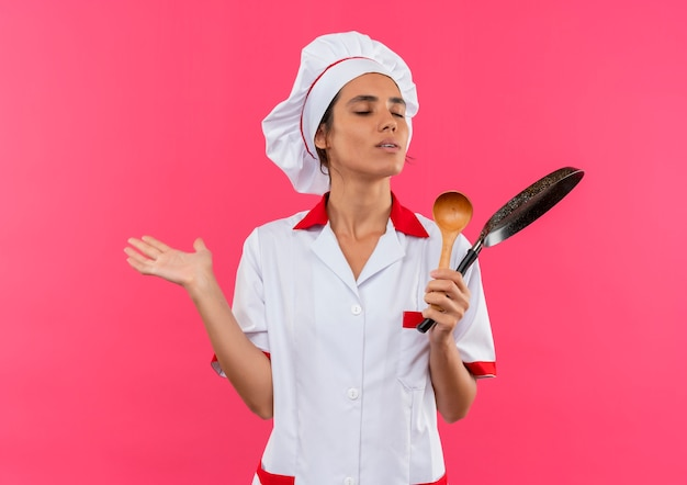 Met gesloten ogen jonge vrouwelijke kok die de pan en de lepel van de chef-kok eenvormige holding met exemplaarruimte draagt