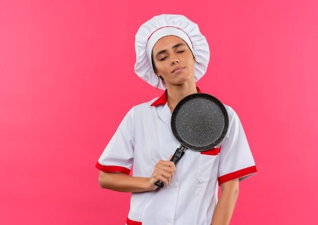 Met gesloten ogen jonge vrouwelijke kok die eenvormige chef-kok draagt die koekenpan op hart met exemplaarruimte zet