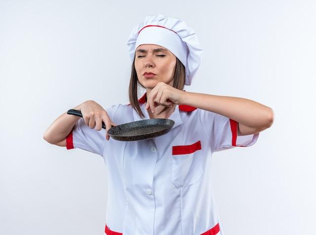 Met gesloten ogen jonge vrouwelijke kok in uniform van de chef-kok met koekenpan geïsoleerd op een witte achtergrond