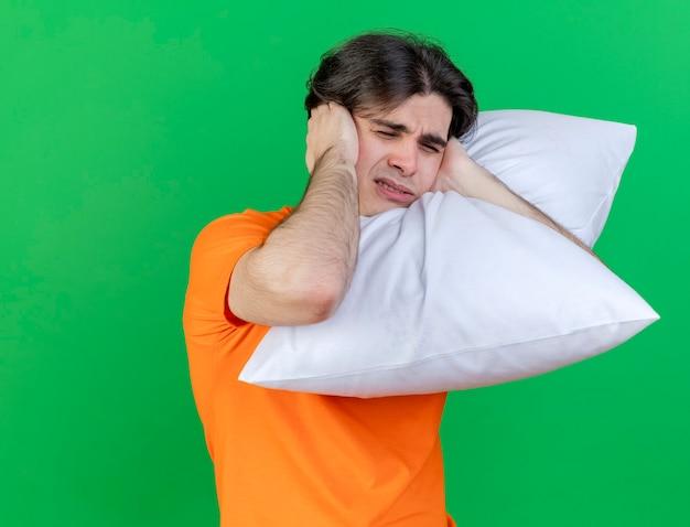 Met gesloten ogen jonge zieke man knuffelde kussen gesloten oren met handen geïsoleerd op groene achtergrond