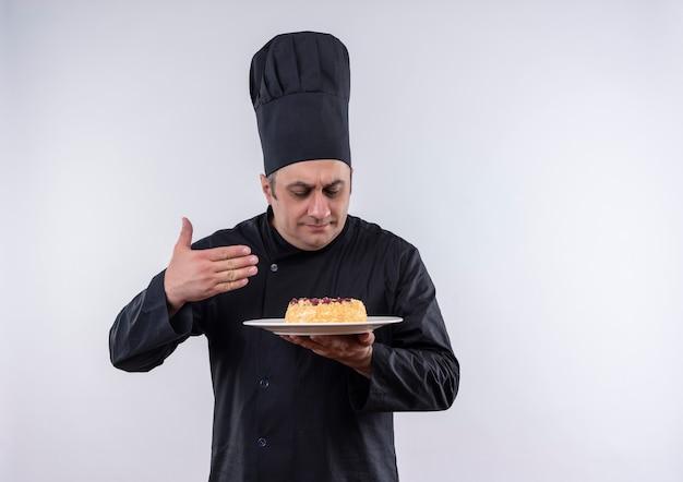 Met gesloten ogen mannelijke kok van middelbare leeftijd in chef-kok eenvormige cake op plaat in zijn hand snuiven